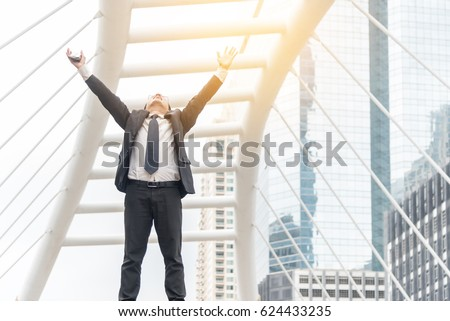 Celebrating success. Low angle view of excited young businessman keeping arms raised and expressing positivity while standing outdoors with office building in the background #624433235