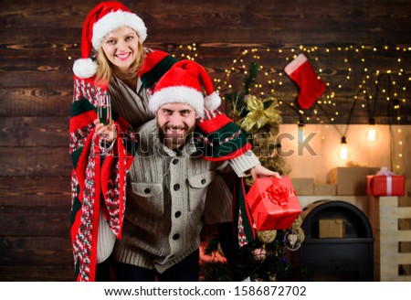Celebrating together. Celebrating winter holiday. Christmas fun. Interesting ideas celebration. Man and woman santa claus hats cheerful celebrating new year. Merry christmas. Guy piggybacking girl.
