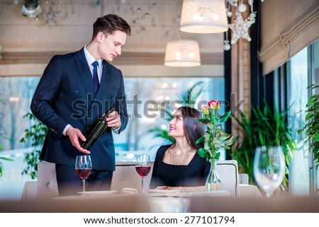 Celebrating together Wedding Anniversary at restaurant. Romantic dinner in the restaurant. Young loving couple visiting the restaurant while the man is holding a bottle of wine and looking at a glass #277101794