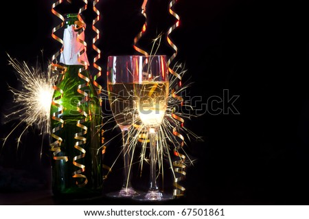 Celebrating with champagne. A bottle with two glasses and hanging ribbons  lit by sparklers glittering through the champagne.