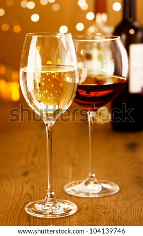 Celebrating with glasses of red and white wine against a sparkling bokeh of festive party lights