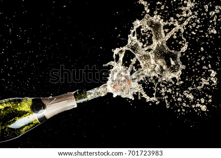 Celebration and holiday theme. Champagne splashes on black background. #701723983