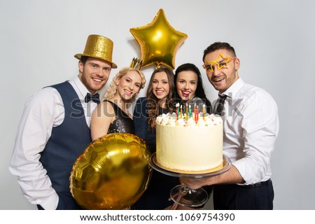 celebration and holidays concept - happy friends with big cake at birthday party