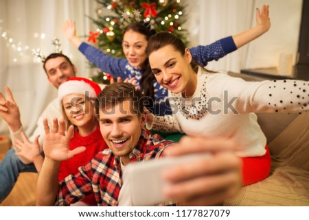 celebration and holidays concept - happy friends with glasses celebrating christmas at home party and taking selfie by smartphone