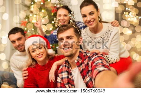 celebration and holidays concept - happy friends with glasses celebrating christmas at home party and taking selfie