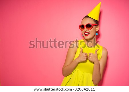 Celebration and party. Having fun. Young pretty woman in yellow dress and birthday hat is laughing. Colorful studio portrait with pink background.