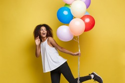 Celebration Concept - Close up Portrait happy young beautiful african woman with white t-shirt running with colorful party balloon. Yellow Pastel studio Background.