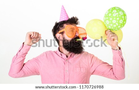 Celebration concept. Guy in party hat with air balloons celebrates. Hipster in giant sunglasses celebrating birthday. Man with beard and mustache on busy face blows into party horn, white background.