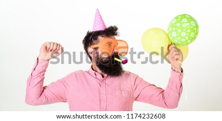 Celebration concept. Guy in party hat with air balloons celebrates. Man with beard and mustache on busy face blows into party horn, white background. Hipster in giant sunglasses celebrating birthday.