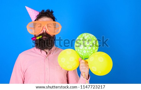 Celebration concept. Hipster in giant sunglasses celebrating birthday. Guy in party hat with air balloons celebrates. Man with beard and mustache on calm face blows into party horn, blue background. #1147723217