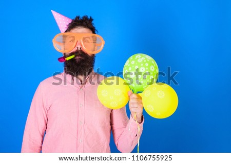 Celebration concept. Hipster in giant sunglasses celebrating birthday. Man with beard and mustache on calm face blows into party horn, blue background. Guy in party hat with air balloons celebrates. #1106755925