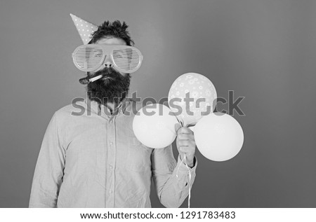 Celebration concept. Hipster in giant sunglasses celebrating birthday. Man with beard and mustache on calm face blows into party horn, blue background. Guy in party hat with air balloons celebrates. #1291783483