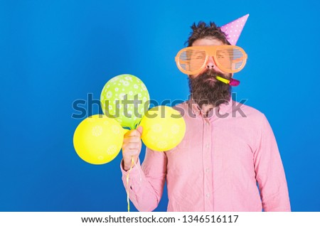 Celebration concept. Hipster in giant sunglasses celebrating birthday. Man with beard and mustache on calm face blows into party horn, blue background. Guy in party hat with air balloons celebrates. #1346516117