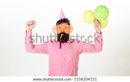 Celebration concept. Man with beard and mustache on busy face blows into party horn, white background. Hipster in giant sunglasses celebrating birthday. Guy in party hat with air balloons celebrates. #1158204151