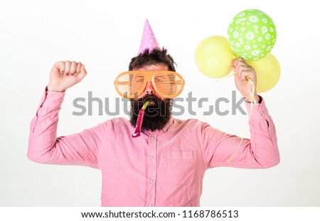 Celebration concept. Man with beard and mustache on busy face blows into party horn, white background. Guy in party hat with air balloons celebrates. Hipster in giant sunglasses celebrating birthday.
