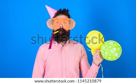 Celebration concept. Man with beard and mustache on calm face blows into party horn, blue background. Hipster in giant sunglasses celebrating birthday. Guy in party hat with air balloons celebrates. #1145210879