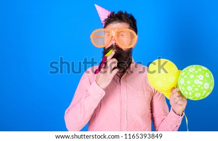 Celebration concept. Man with beard and mustache on calm face blows into party horn, blue background. Guy in party hat with air balloons celebrates. Hipster in giant sunglasses celebrating birthday.