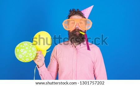 Celebration concept. Man with beard and mustache on calm face blows into party horn, blue background. Hipster in giant sunglasses celebrating birthday. Guy in party hat with air balloons celebrates. #1301757202