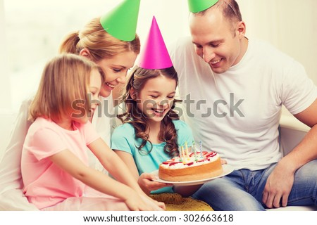 celebration, family, holidays and birthday concept - happy family with two kids in hats with cake at home