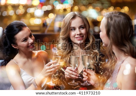 celebration, friends, bachelorette party and holidays concept - happy women with champagne glasses at night club #411973210