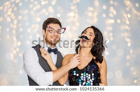 celebration, fun and holidays concept - happy couple posing with party props over festive lights background #1024135366