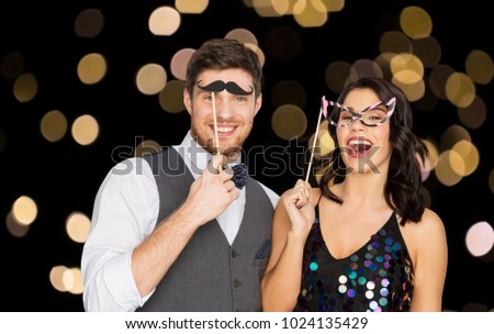 celebration, fun and holidays concept - happy couple posing with party props over lights on black background