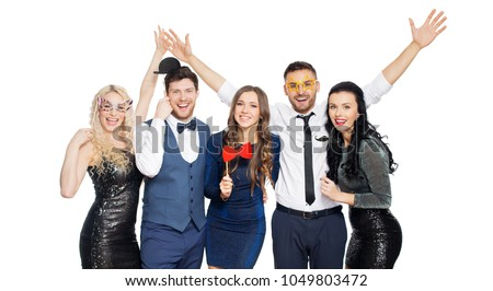 celebration, fun and holidays concept - happy friends posing with party props