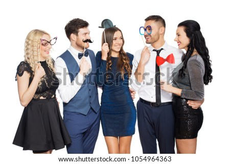 celebration, fun and holidays concept - happy friends posing with party props #1054964363