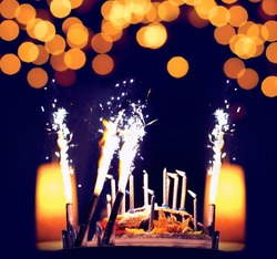 Celebration, holiday birthday cake with candles and fireworks, bright lights bokeh