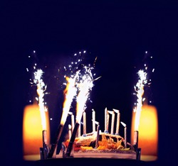 Celebration, holiday birthday cake with candles and fireworks, bright lights bokeh on a black background