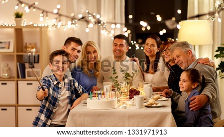 celebration, holidays and people concept - happy family having birthday tea party at home and taking picture by smartphone on selfie stick