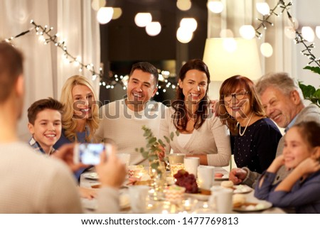 celebration, holidays and people concept - happy family having tea party and photographing by smartphone at home