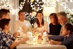 celebration, holidays and people concept - happy family with sparklers having tea party at home