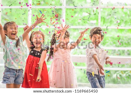 Celebration New Year Party concept. Group of children having fun at birthday party. Little girl and boy enjoy with cake in party.  #1169665450