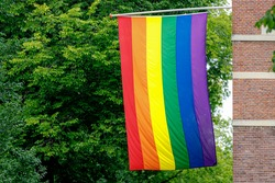Celebration of Gay Pride in Amsterdam with rainbow flag hanging outside building along street, The sybol of gay, lesbian, bisexaul and trangender, LGBT social movments in Netherlands.