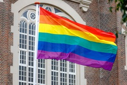 Celebration of Gay Pride in Amsterdam with rainbow flags hanging outside building along street, LGBT annual festival to celebrate that we can be who we are and love, Netherlands.
