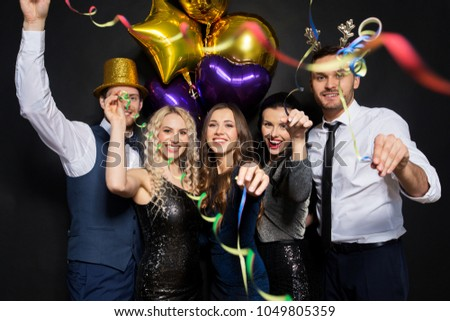 celebration, people and holidays concept - happy friends at christmas or new year party with balloons and serpentine over black background