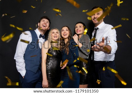 celebration, people and holidays concept - happy friends at party under golden confetti over black background #1179101350