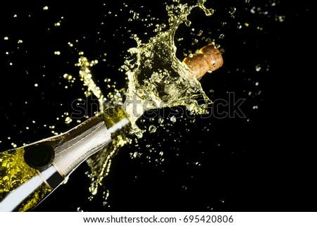 Celebration theme with splashing champagne, isolated on black background.