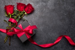 Celebration valentines day with rose flower bouquet and black gift box over stone background.