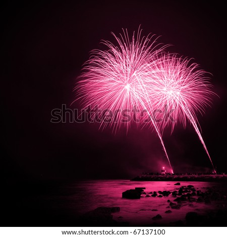 Celebration with colorful fireworks over the sea near a marina