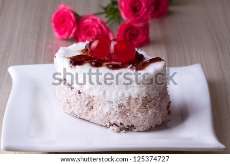 Celebratory cake with cherries on a background of pink roses - stock photo