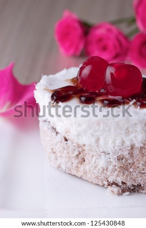 Celebratory cake with cherries on a background of pink roses