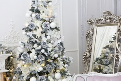 Celebratory New Year tree decorated with beautiful fur-tree toys and Christmas gifts in gift packages and celebratory boxes