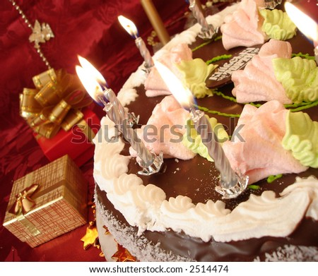 celebratory table (birthday cake and candles, gift boxes) on red