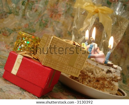 celebratory table (piece of birthday cake and blue candle, two glasses with champagne, gift boxes)
