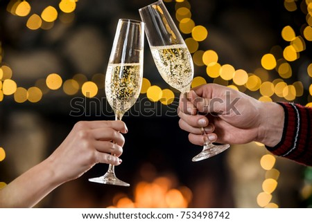 Celebreating christmas and new year. Couple keeps and toasts champagne glasses