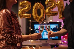 Celebreating Virtual Christmas New Year's Eve party at home during Covid-19 pandemic. How to celebrate and decorate for 2021 home with balloons. Couple holding and toasting champagne glasses