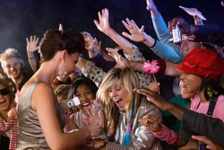 Celebrity signing autograph for screaming fans