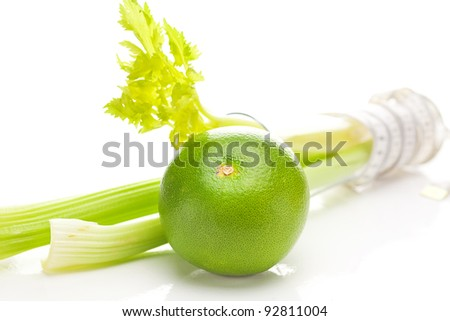 celery in a tall glass, green grapefruit and measure tape isolated on white